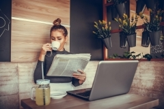 Beautiful young woman reading newspaper and drinking coffee  in coffee shop